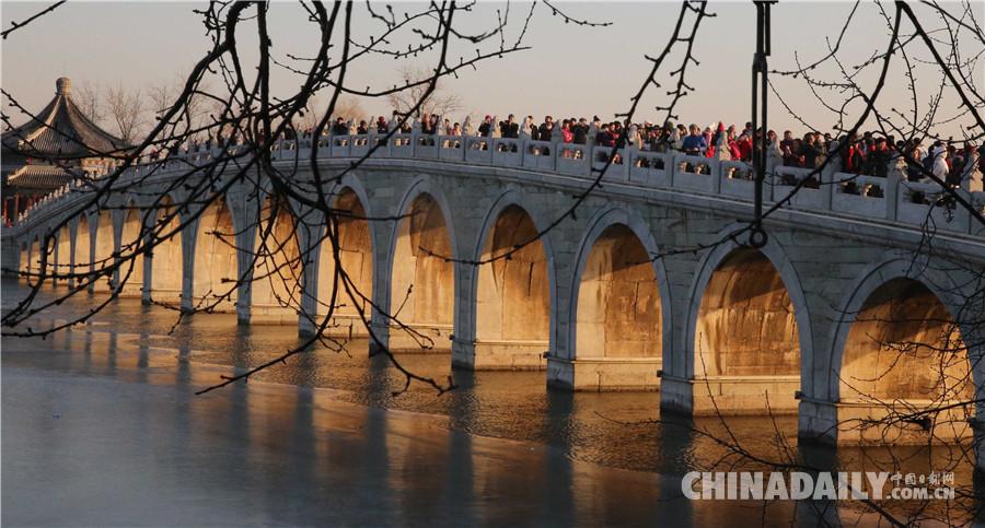 游客在颐和园欣赏十七孔桥金光穿洞美景。 中国日报记者 姜东 摄 中国日报12月21日电 2017年12月21日日落时分,北京颐和园十七孔桥出现金光穿洞美景,吸引许多游客前来观赏。 (编辑:涂恬 黄河流)